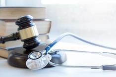 Ein Richterhammer mit einem Stethoskop als Symbol für Medizinrecht.