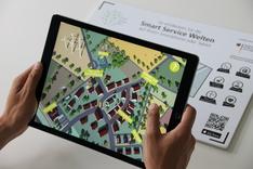 """Dieses Bild zeigt die """"Smart Service Welten in AR""""-App in Aktion auf einem Tablet. Im Hintergrund der für die App notwendige Augmented-Reality-Tracking-Flyer."""