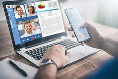 Dieses Bild zeigt einen Laptop mit laufender Videokonferenz und geöffnetem Textdokument. Der Nutzer hält ein Smartphone in der Hand.