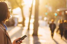 Dieses Bild zeigt das Covermotiv der Kurzstudie Open Public Data in Deutschland: Eine Frau hält ein Smartphone und blickt in die Sonne. Im Hintergrund Passanten, die aus einem Bus aussteigen.